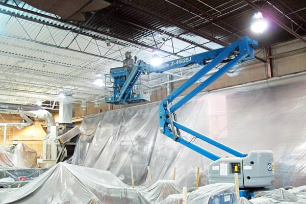 painter spray painting a metal deck ceiling in a factory