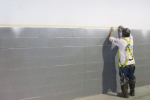 Dearborn, Michigan painter spray painting an industrial building wall